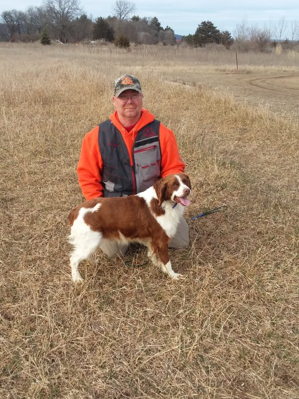 Man wearing orange hoodie with a Brittany Spaniel dog standing in front of him